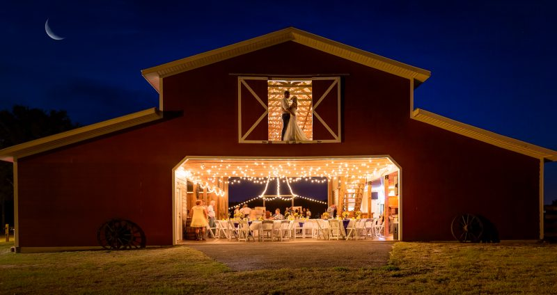 Bride and groom in hay loft of barn during the night