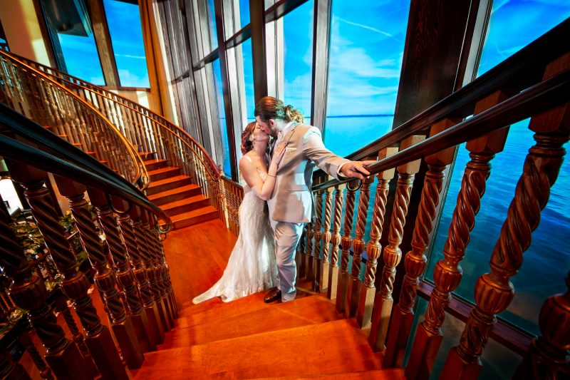 Bride and Groom kissing on stairs at Tavares Pavilion on the Lake